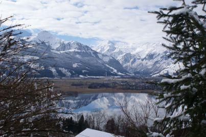 Im See spiegeln sich der Hohe Tenn, das Imbachhorn und das Kitzsteinhorn (mit dem Gipfel in den Wolken).