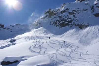 Der Pulverschnee wird von einer Windbö von den Gipfeln geblasen.