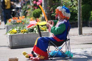 Straßenkünstler, wie dieser Clown, bieten ihre Dienste an.