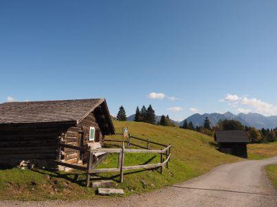 Viele kleine Hütten sind auf der Alpe Rona am Wegesrand zu sehen.