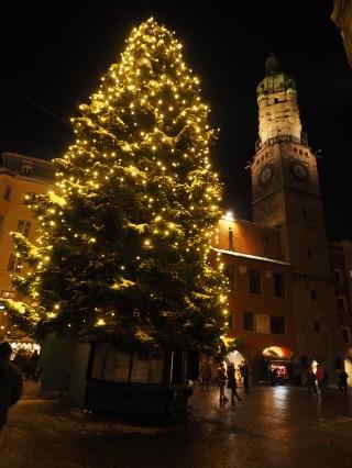Vor dem goldenen Dachl steht ein imposanter Christbaum und der Stadtturm blickt auf das Treiben am Weihnachtsmarkt herunter.